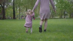 到处乱跑用藏品手的母亲和小女儿在惊人的绿色公园 使用在公园的妇女和孩子 股票录像