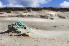 到处自然:在沙子海岸线的老被摩擦的绳索在低tid 库存图片