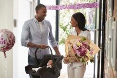 到家与新出生的婴孩的父母在汽车座位 免版税库存照片