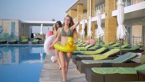 到有可膨胀的圆环的游泳衣里走和跳舞在蓝色水池附近的快乐的女朋友愉快的公司在期间 影视素材