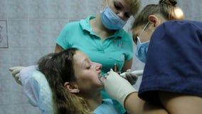到牙医正牙医生医生的参观有助理的设定了一名妇女的铁括号有一牙齿fixator的 股票视频