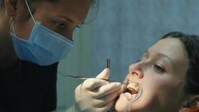 到牙医的参观,托架系统的设施 正牙医生在牙齿改正集合托架并且看 股票视频