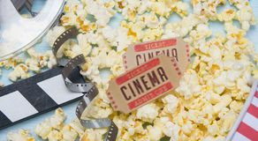 到电影的两张票,以玉米花和影片为背景 库存照片
