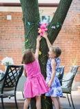 到达一个复活节彩蛋的两个女孩尝试在树 免版税库存图片