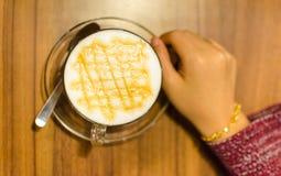 到达一个杯子热的焦糖咖啡macchiato的妇女手 selec 库存图片
