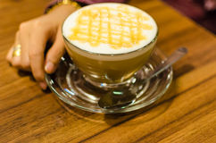 到达一个杯子热的焦糖咖啡macchiato的妇女手 selec 免版税库存图片