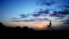 到达上面的山骑自行车的人庆祝与举他的自行车到在惊人的晚上光的天空 股票录像