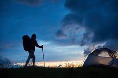 到达与拐杖的上面和旅游背包的年轻女性登山人在山的日落在罗马尼亚 库存图片