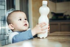 到达为在塑料瓶的桌上的牛奶的美丽的婴孩 免版税库存照片