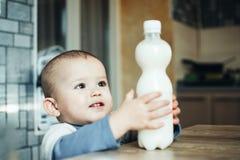 到达为在塑料瓶的桌上的牛奶的美丽的婴孩 免版税库存图片