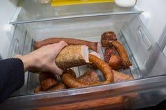 到达为在开放冰箱的食物的人的手 库存图片