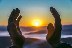 到达为太阳在日出,特写镜头的一个老人的手 诞生新的生活的概念 免版税库存图片