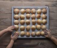 到达为新鲜的被烘烤的小圆面包的孩子的手 免版税库存图片