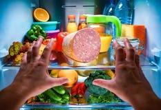 到达为食物的人的手在开放冰箱的晚上 免版税图库摄影