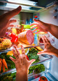 到达为食物的人的手在开放冰箱的晚上 免版税库存照片