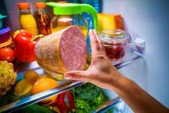 到达为食物的人的手在开放冰箱的晚上 库存图片