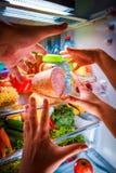 到达为食物的人的手在开放冰箱的晚上 库存照片
