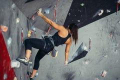 到达人为bouldering的墙壁的上面妇女,当行使在健身房时 免版税库存图片