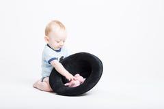 到达入填充动物玩偶的黑帽会议的婴孩 免版税库存照片