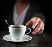 到达咖啡杯的 免版税库存照片