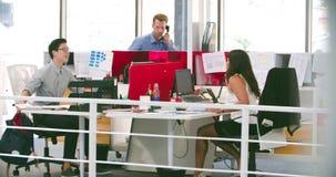 到达在办公室和坐在书桌的商人 影视素材