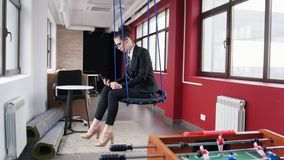 到达天空的企业概念金黄回归键所有权 玻璃的一名妇女坐摇摆在办公室,听音乐和看屏幕 股票录像