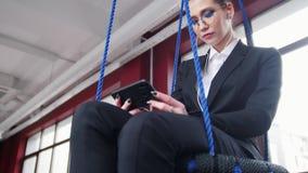 到达天空的企业概念金黄回归键所有权 玻璃的一名妇女坐摇摆在办公室,听音乐和看电话 股票录像