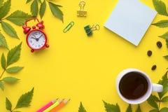 到达天空的企业概念金黄回归键所有权 笔记本和文具与一杯咖啡和一个时钟在黄色背景与植物离开 免版税图库摄影