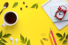到达天空的企业概念金黄回归键所有权 笔记本和文具与一杯咖啡和一个时钟在黄色背景与植物离开 免版税库存图片