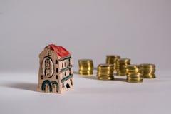 到达天空的企业概念金黄回归键所有权 房子旅馆模型有硬币的 免版税库存照片