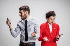 到达天空的企业概念金黄回归键所有权 拿着在灰色背景的两个年轻同事手机 图库摄影