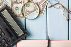 到达天空的企业概念金黄回归键所有权 有玻璃、美金、笔记本、钢笔和计算器的放大镜在蓝色木背景 库存图片