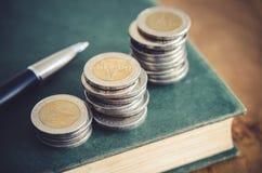 到达天空的企业概念金黄回归键所有权 特写镜头堆硬币、笔和旧书在ta 免版税库存照片
