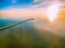 到达太阳的长的木码头在壮观的日落 免版税库存照片