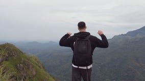 到达山和伸出的胳膊上面的男性远足者  有站立在边缘的背包的年轻人游人 股票视频