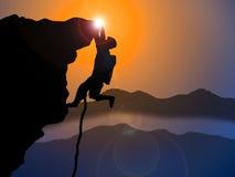 到达峭壁上面的爬山者 免版税库存照片