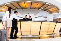 到达旅馆服务台的亚洲中国夫妇 库存图片