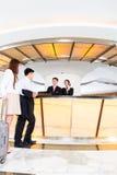到达旅馆服务台的亚洲中国夫妇 免版税库存照片
