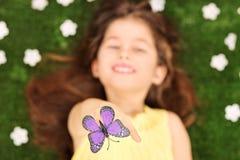 到达的小女孩放置在草甸和接触蝴蝶 免版税图库摄影