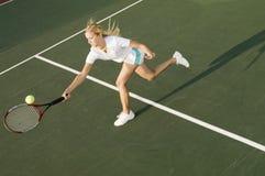 到达的网球员击中球 免版税库存图片