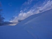 到达登上Catria的山顶远足者在冬天在日落,翁布里亚,亚平宁山脉,意大利 免版税库存照片