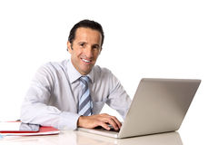 40到50岁研究计算机的资深商人在看起来的办公桌确信和轻松 库存照片