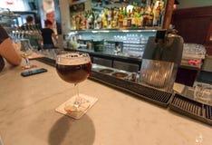 制作在老时髦的玻璃的啤酒在餐馆酒吧柜台有访客和侍酒者的 免版税库存图片