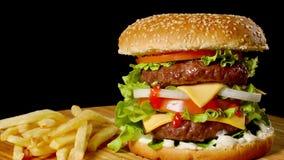 制作牛肉汉堡和炸薯条在黑背景隔绝的木桌上 股票录像