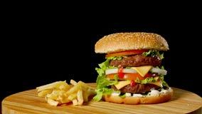 制作牛肉汉堡和炸薯条在黑背景隔绝的木桌上 股票视频