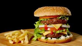 制作牛肉汉堡和炸薯条,在黑背景隔绝的调味汁 快餐 股票视频