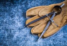 制图圆规在被抓的金属背景c的安全手套 库存照片
