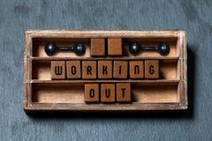 制定出健身房概念标题 年迈的箱子,与老牌信件,黑哑铃的木立方体 被构造的灰色石头 免版税库存照片