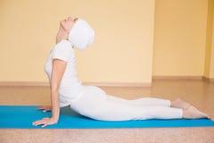 制定出瑜伽锻炼bhujangasana (眼镜蛇姿势)在健身席子的美丽的妇女全长画象 免版税库存图片