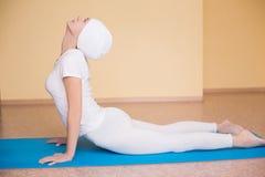制定出瑜伽锻炼bhujangasana (眼镜蛇姿势)在健身席子的美丽的妇女全长画象 免版税图库摄影